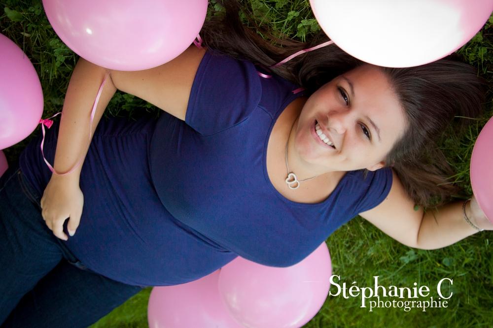 Femme enceinte couchée dans gazon avec ballon rose