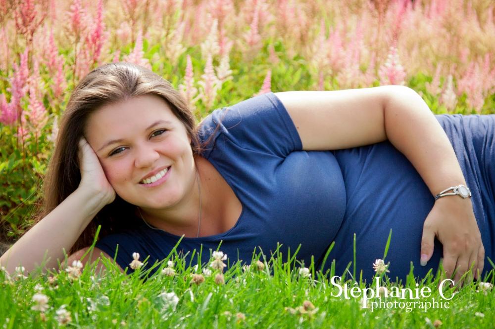 Femme enceinte avec chandail bleu couchée dans gazon avec fleurs roses