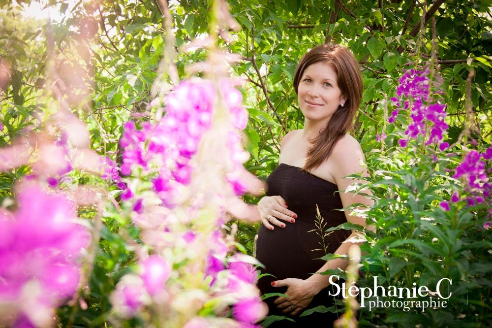 Femme enceinte avec robe noire dans un champs de fleurs