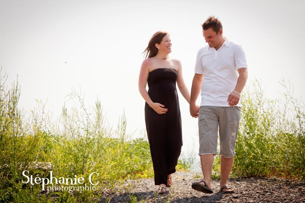 Couple qui marche sur le bord de la mer en Gaspésie avec femme enceinte en robe longue noire