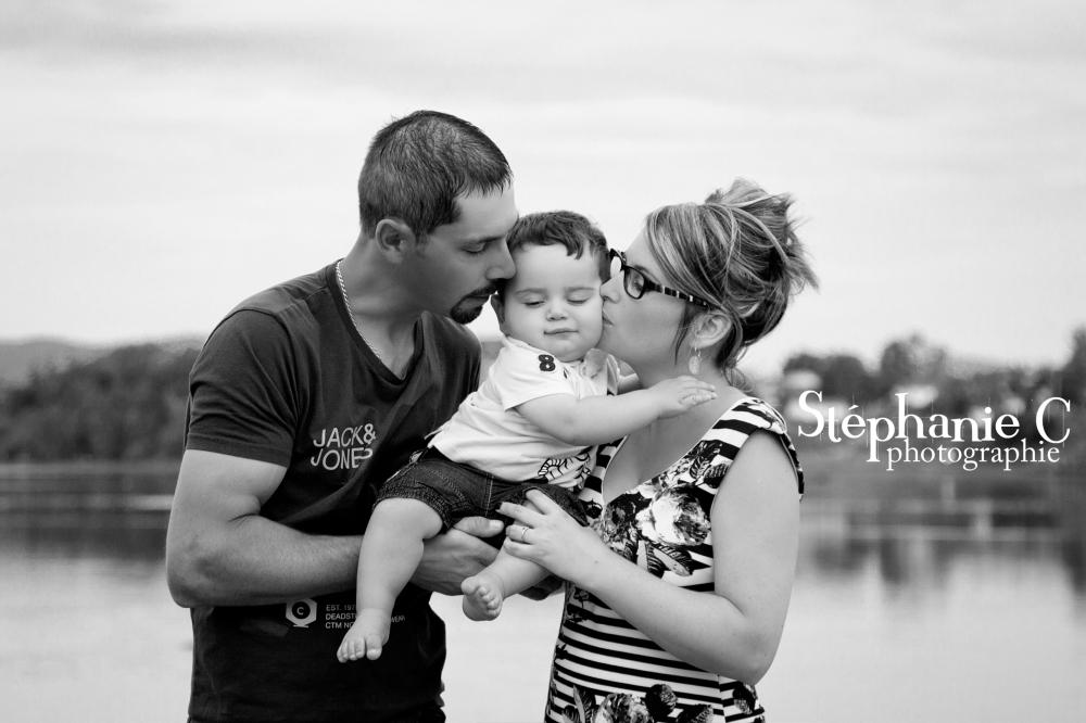 photo noir et blanc de parents qui embrassent un bébé
