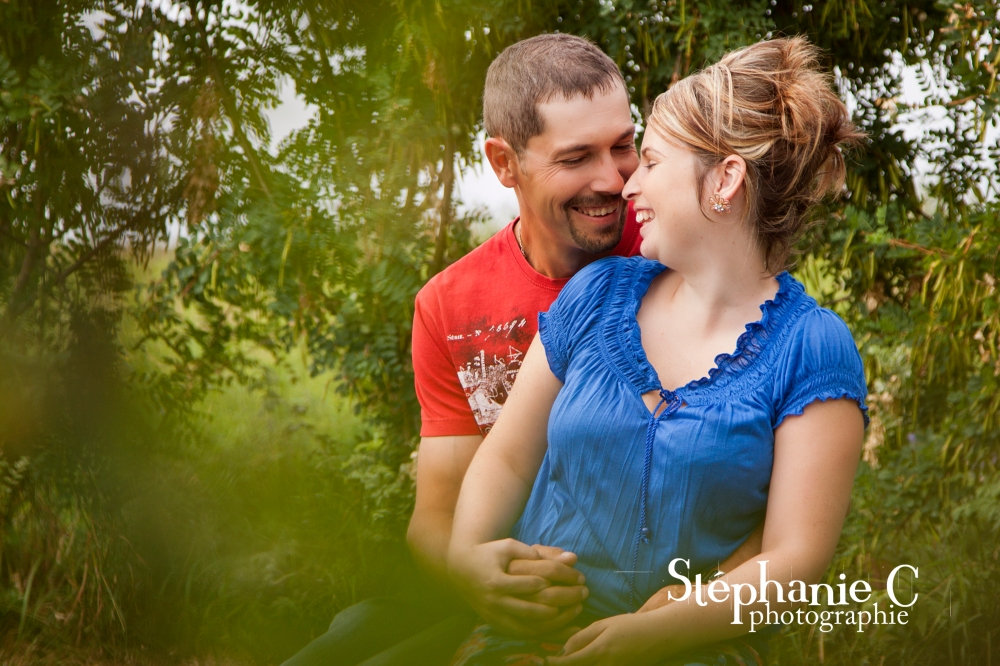 Couple souriant sur un banc de parc avec verdure