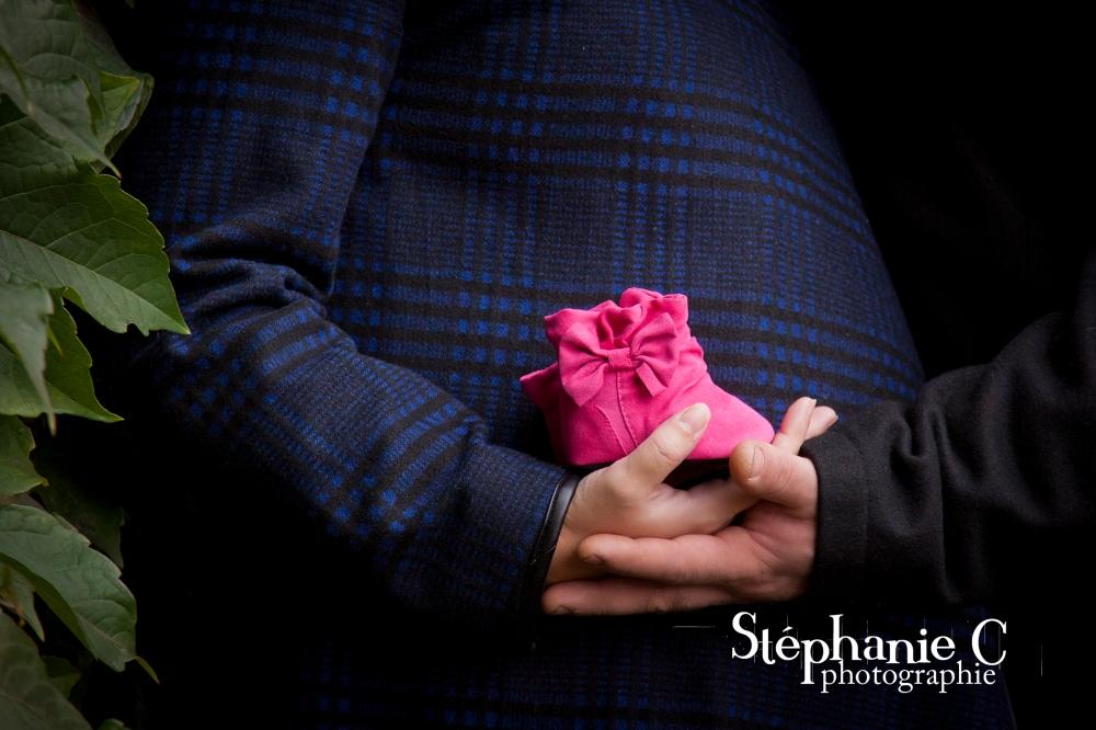 ventre femme enceinte avec main du conjoint tenant un petit chausson de bébé rose