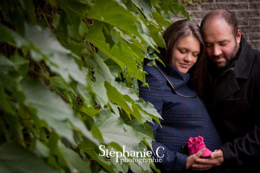 couple tenant un chausson de bébé rose devant mur de végétation