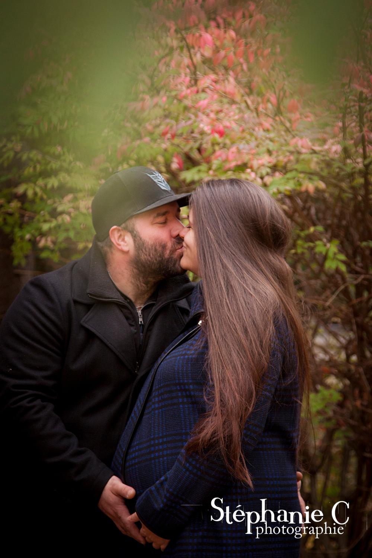 couple avec femme enceinte qui s'embrasse dans la nature